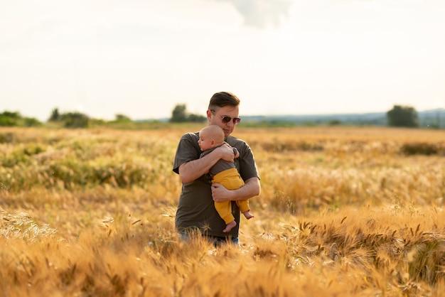 Jonge vader houdt zijn drie maanden oude zoon in zijn armen