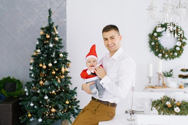 Jonge vader houdt zijn zoon in een klein kerstmankostuum