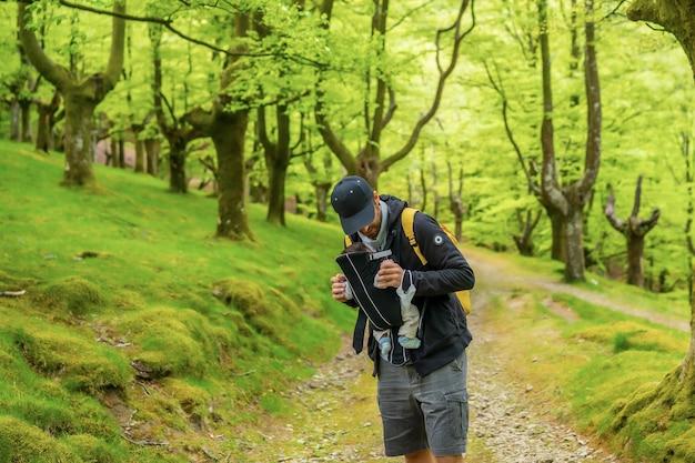 Jonge vader loopt met zijn pasgeboren kind op een pad in het bos