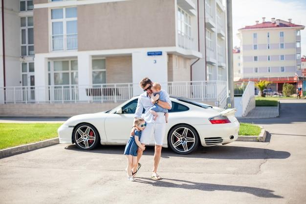 Jonge vader loopt met zijn twee dochters op de achtergrond van een sportwagen
