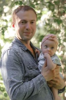 Jonge vader met kleine dochter buiten in de lente natuur. hoge kwaliteit foto.