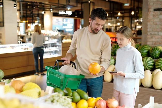 Jonge vader met mand die zijn dochter overlegt terwijl hij allebei rijpe meloen of pompoen in supermarkt kiest