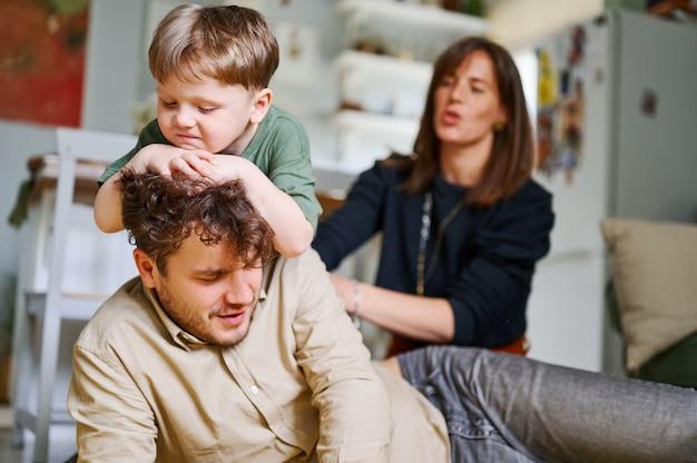Jonge vader met plezier met liedjes spelen en lachen thuis gelukkig gezin tijd samen doorbrengen