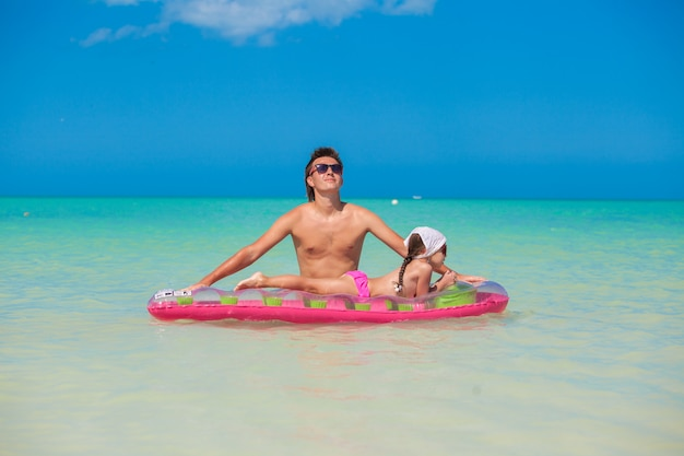 Jonge vader met schattige dochter op een luchtbed in de zee