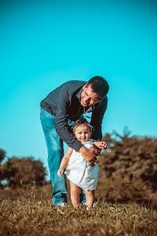 Jonge vader met zijn dochter die buiten in een park speelt Premium Foto