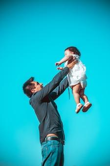 Jonge vader met zijn dochter die buiten in een park speelt