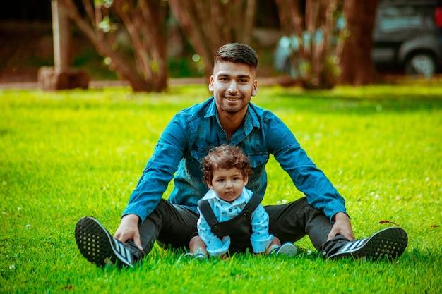Jonge vader met zijn zoon zittend op het gras