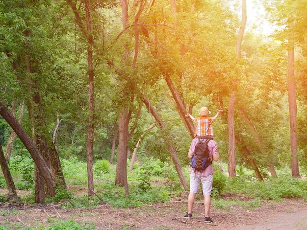Jonge vader met zoon op schouders die zich tegen een achtergrond van groen bos bevinden. achteraanzicht. zonlicht.