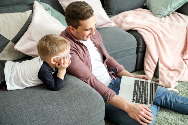 Jonge vader met zoontje kijken naar tekenfilms thuis