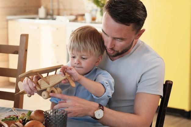 Jonge vader speelt met zijn zoontje terwijl ze aan de eettafel in de keuken zitten