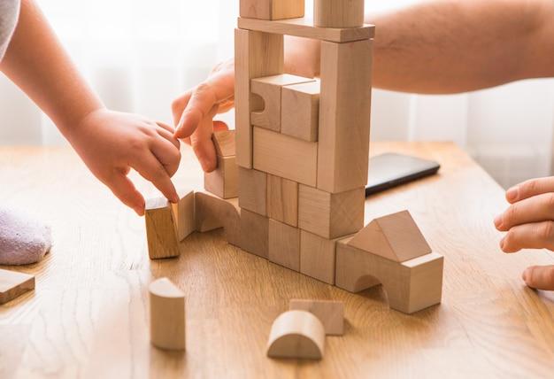 Jonge vader spelen met bakstenen bouwen met zoontje