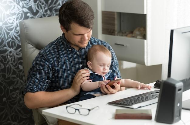 Jonge vader werkt op de computer en speelt met zijn zoontje