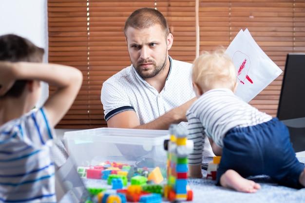 Jonge vader zakenman ouder onderbreekt door haar kinderen zonen tijdens het werken in huis.