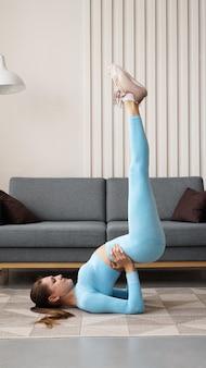 Jonge vastberaden zelfverzekerde slanke vrouw die oefeningen thuis doet. fitnesstrainer traint thuis tijdens quarantaine. licht modern interieur