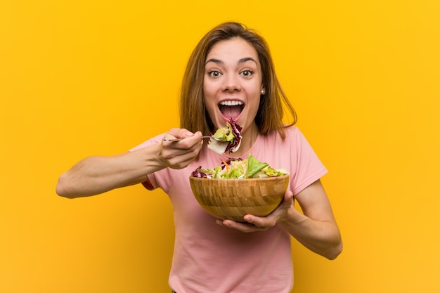 Jonge veganistvrouw die een verse en heerlijke salade eet
