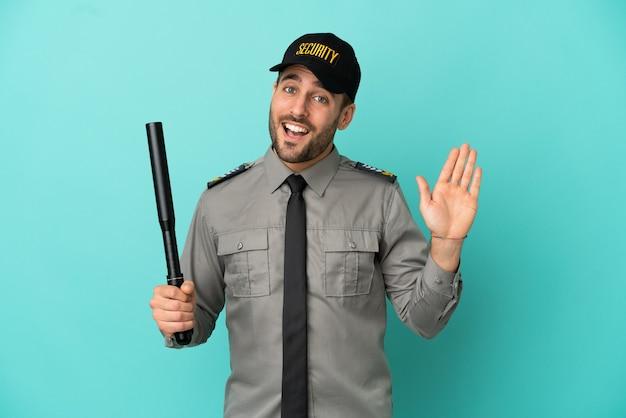 Jonge veiligheidsman geïsoleerd op blauwe achtergrond saluerend met de hand met gelukkige uitdrukking