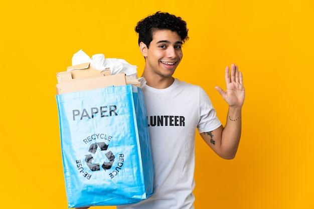Jonge venezolaanse man die een recyclingzak vol papier vasthoudt om te recyclen, saluerend met de hand met een blije uitdrukking