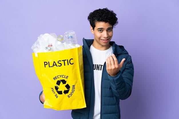Jonge venezolaanse man die een zak vol plastic flessen vasthoudt die uitnodigt om met de hand te komen. blij dat je gekomen bent