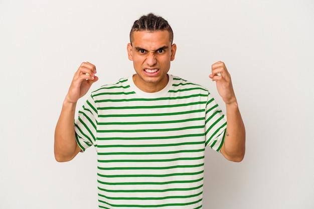 Jonge venezolaanse man geïsoleerd op een witte achtergrond boos schreeuwen met gespannen handen.