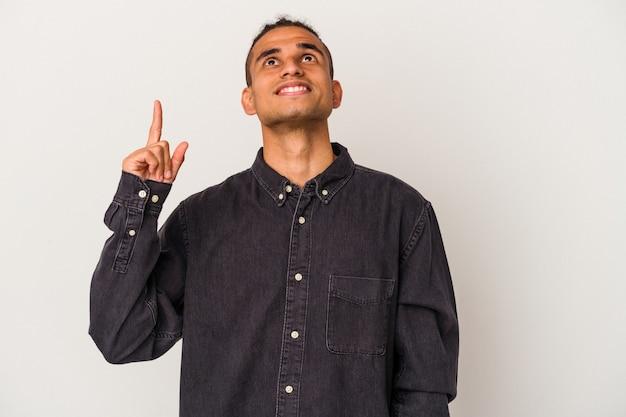 Jonge venezolaanse man geïsoleerd op een witte achtergrond geeft aan met beide voorvingers omhoog met een lege ruimte.
