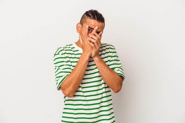 Jonge venezolaanse man geïsoleerd op een witte achtergrond knipperen door vingers bang en nerveus.