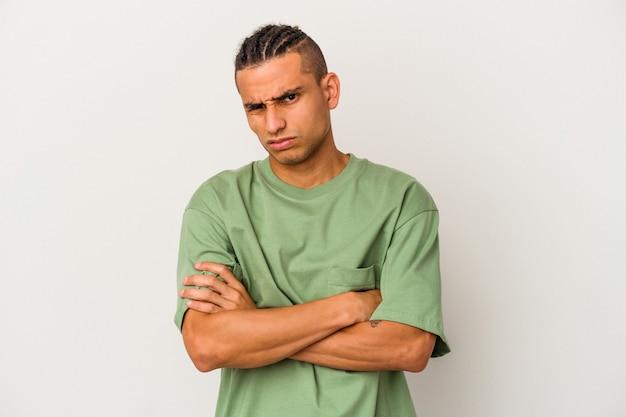 Jonge venezolaanse man geïsoleerd op een witte muur ongelukkig op zoek met sarcastische uitdrukking.