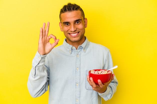 Jonge venezolaanse man met een kom met granen geïsoleerd op gele achtergrond