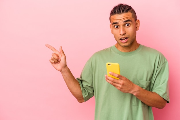Jonge venezolaanse man met een mobiele telefoon geïsoleerd op een roze achtergrond die naar de zijkant wijst