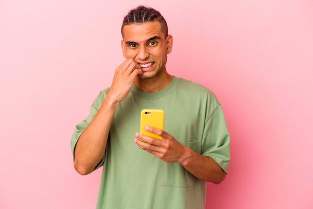 Jonge venezolaanse man met een mobiele telefoon geïsoleerd op een roze achtergrond die vingernagels bijt, nerveus en erg angstig.