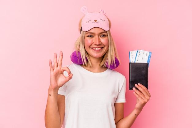 Jonge venezolaanse reiziger vrouw met een paspoort geïsoleerd op roze achtergrond vrolijk en zelfverzekerd weergegeven: ok gebaar.