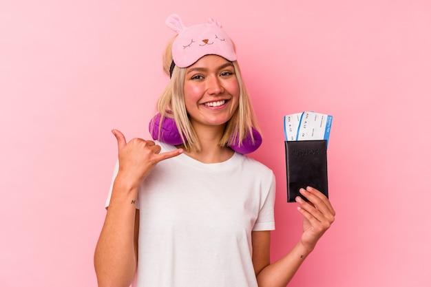 Jonge venezolaanse reizigersvrouw die een paspoort houdt dat op roze muur wordt geïsoleerd die een mobiel telefoongesprekgebaar met vingers toont.