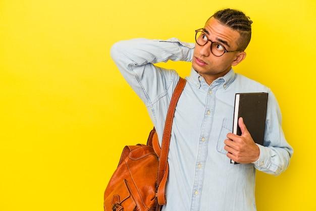 Jonge venezolaanse student man geïsoleerd op gele achtergrond achterhoofd aanraken, denken en een keuze maken.