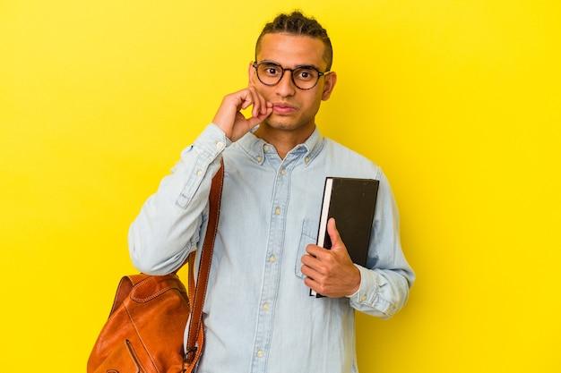 Jonge venezolaanse studentenmens die op gele achtergrond met vingers op lippen wordt geïsoleerd die een geheim houden.