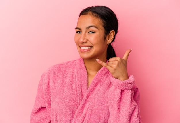 Jonge venezolaanse vrouw die een badjas draagt die op roze achtergrond wordt geïsoleerd die een mobiel telefoongesprekgebaar met vingers toont.