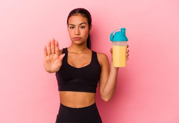 Jonge venezolaanse vrouw die een eiwitshake drinkt die op roze achtergrond wordt geïsoleerd