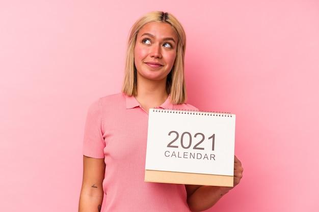 Jonge venezolaanse vrouw die een kalender houdt die op roze muur wordt geïsoleerd en droomt van het bereiken van doelstellingen en doeleinden