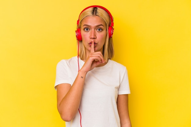 Jonge venezolaanse vrouw die muziek luistert die op gele achtergrond wordt geïsoleerd die een geheim houdt of om stilte vraagt.
