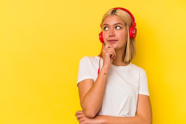 Jonge venezolaanse vrouw die muziek luistert die op gele achtergrond wordt geïsoleerd en zijwaarts kijkt met twijfelachtige en sceptische uitdrukking.