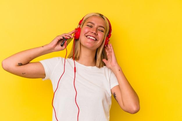 Jonge venezolaanse vrouw die muziek luistert die op gele achtergrond wordt geïsoleerd