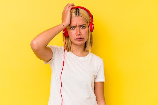 Jonge venezolaanse vrouw die muziek luistert die op gele muur wordt geïsoleerd die geschokt wordt, heeft zij belangrijke vergadering herinnerd.