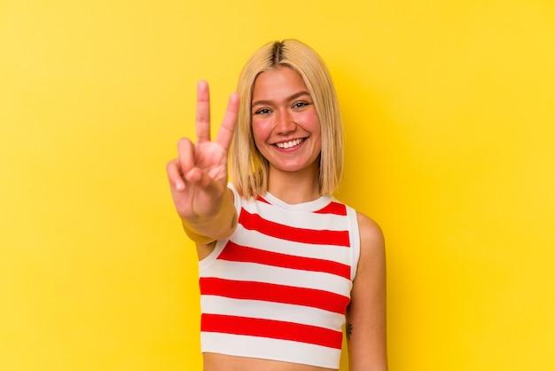 Jonge venezolaanse vrouw die op gele achtergrond wordt geïsoleerd die overwinningsteken toont en breed glimlacht.