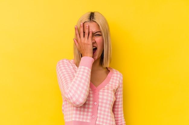 Jonge venezolaanse vrouw die op gele muur wordt geïsoleerd die pret heeft die de helft van het gezicht bedekt met palm.