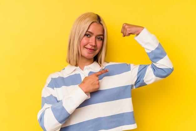 Jonge venezolaanse vrouw die op gele muur wordt geïsoleerd die sterktegebaar met wapens toont, symbool van vrouwelijke macht