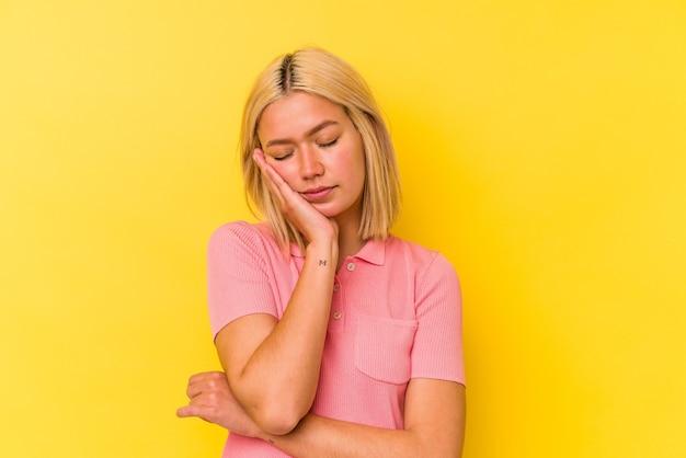 Jonge venezolaanse vrouw die op gele muur wordt geïsoleerd die verveeld, vermoeid is en een ontspannende dag nodig heeft.