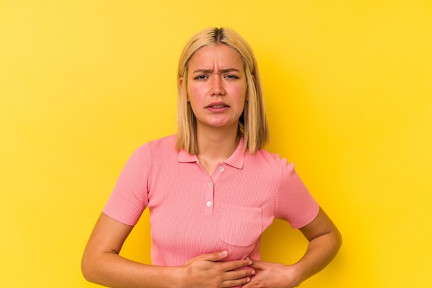 Jonge venezolaanse vrouw die op gele muur wordt geïsoleerd met leverpijn, buikpijn.