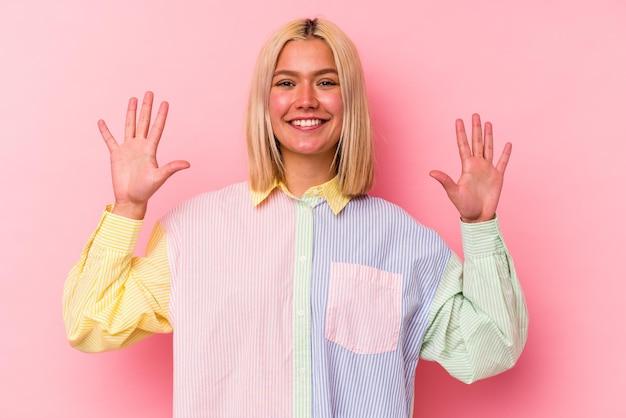 Jonge venezolaanse vrouw die op roze muur wordt geïsoleerd die nummer tien met handen toont.