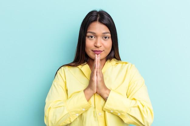 Jonge venezolaanse vrouw geïsoleerd op blauwe achtergrond bidden, toewijding tonen, religieuze persoon op zoek naar goddelijke inspiratie.
