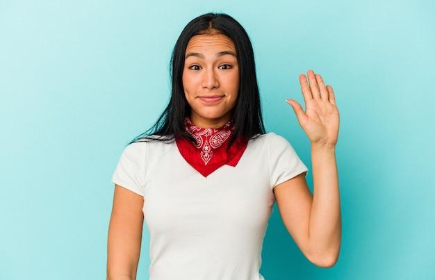 Jonge venezolaanse vrouw geïsoleerd op blauwe achtergrond glimlachend vrolijk met nummer vijf met vingers.