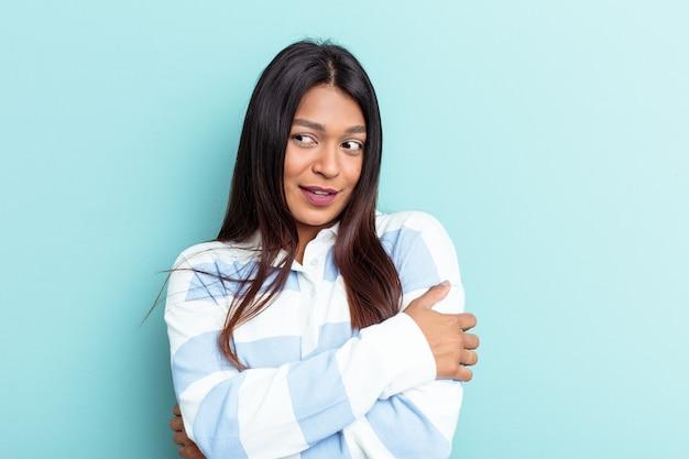 Jonge venezolaanse vrouw geïsoleerd op blauwe achtergrond glimlachend zelfverzekerd met gekruiste armen.