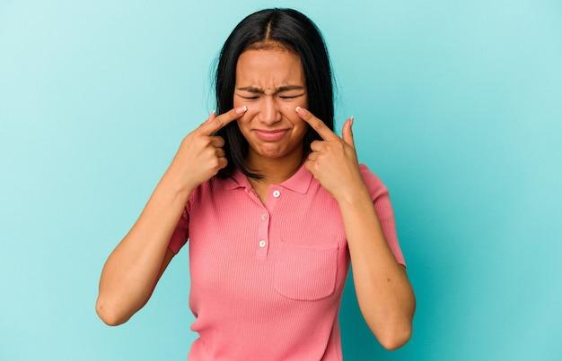 Jonge venezolaanse vrouw geïsoleerd op blauwe achtergrond huilen, ongelukkig met iets, pijn en verwarring concept.
